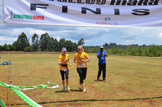 Robin crosses the finish line at the Rift Valley Marathon with a little encouragement and run-a-long by Dana